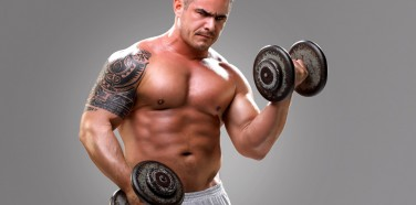 Bodybuilder with a tattoo lifting dumbells, closeup